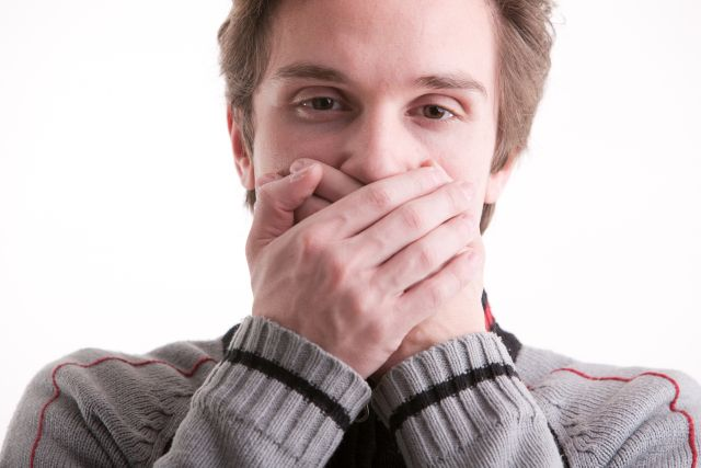young man showing he can't speak (hands on mouth)