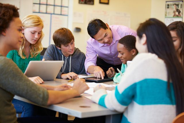 High School Students With Teacher In Class Using Laptops
